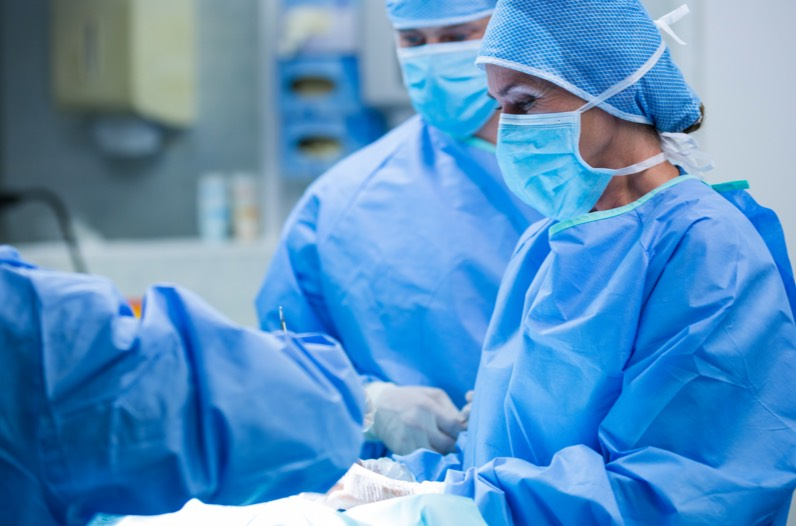 A surgeon's face behind a surgical mask and other doctors performing a procedures
