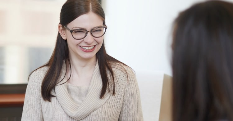 A woman with dark hair and glasses smiling at someone