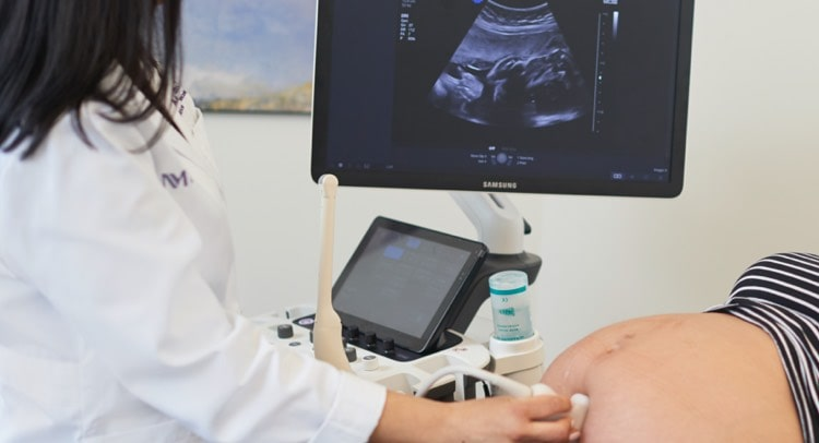 A technician performing an ultrasound on a pregnant woman
